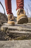 A menina anda ao longo da ponte de madeira podre velha em botas à moda imagem de stock