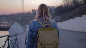 A menina anda ao longo do passeio da cidade no fundo de um por do sol bonito Gerencie para a câmera diversas vezes A c?mera vídeos de arquivo