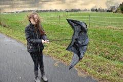 A menina anda através da chuva e a tempestade, seu guarda-chuva é quebrada imagens de stock