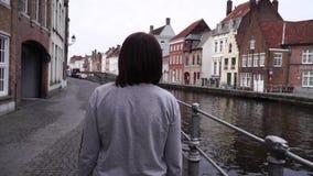 A menina anda e olha atrações na cidade de Bruges Bélgica Movimento lento video estoque