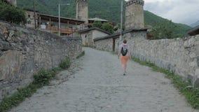 A menina anda na cidade velha Mestia, Geórgia vídeos de arquivo