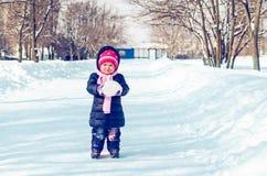 A menina anda no inverno em uma aleia nevado imagens de stock royalty free