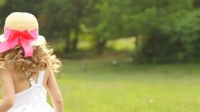 A menina anda no parque e gerencie ao redor em um círculo Movimento lento vídeos de arquivo