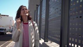 A menina anda nos fones de ouvido em torno da cidade vídeos de arquivo