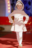 A menina anda pista de decolagem durante o desfile de moda dos miúdos imagem de stock