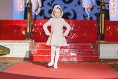 A menina anda pista de decolagem durante o desfile de moda dos miúdos de Stillini imagens de stock royalty free