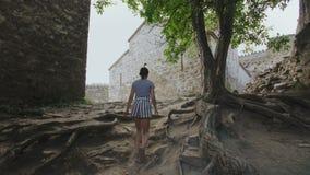 A menina anda trajeto no território da fortaleza defensiva antiga em torno de uma igreja nas montanhas Geórgia vídeos de arquivo
