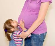 A menina aninha-se em um estômago da mãe grávida Fotos de Stock Royalty Free