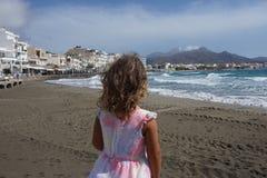 A menina 3-4-ano-velha olha a frente mar?tima de Ierapietra na Creta, Gr?cia foto de stock royalty free