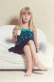 Menina 5 anos de assento velho em um sofá com copo Fotos de Stock