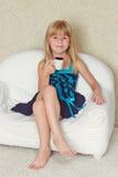 Menina 5 anos de assento velho em um sofá com copo Imagens de Stock