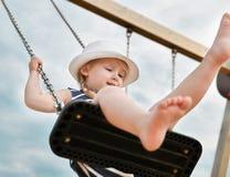 Menina 3 anos de equitação velha em um balanço Foto de Stock