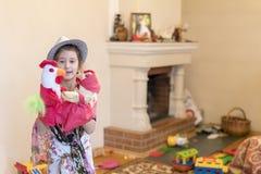 Menina 8 anos de jogo velho com as bonecas no fundo da chaminé imagem de stock