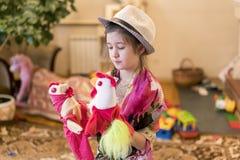 Menina 8 anos de jogo velho com as bonecas no fundo da chaminé imagens de stock royalty free