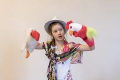 Menina 8 anos em um chapéu que joga bonecas de pano Mostra de fantoche Corvo e galo Brinquedos criativos imagens de stock royalty free
