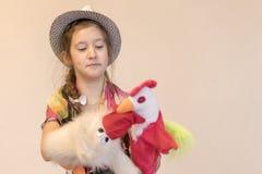 menina 8 anos no chapéu que joga no teatro do fantoche Contra um fundo claro Copie o espaço imagens de stock