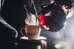 A menina 20 anos velha derrama o chá preto da chaleira de vidro para colocar imagem de stock