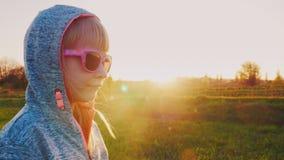 Menina 6 anos velha em um fato de esporte encapuçado Estando contra o fundo do por do sol, vidros rosados vestindo dos óculos de  filme