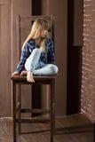 A menina 6 anos velha nas calças de brim e em uma camisa azul está sentando-se na cadeira alta Imagem de Stock Royalty Free