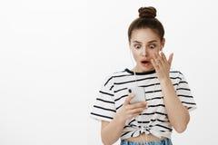Menina ansiosa após ter enviado o tiro de tela da conversação à pessoa errada Shocked surpreendeu a mulher caucasiano nova com bo imagens de stock royalty free