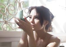 Menina antes do espelho para aplicar a composição Foto de Stock Royalty Free