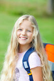 A menina ao ar livre com saco de escola vai ao sorriso da escola Foto de Stock