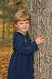 Menina ao lado da árvore fotos de stock