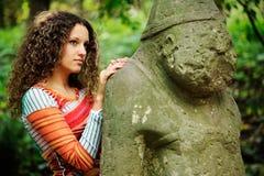 A menina ao lado de um ídolo de pedra Fotografia de Stock