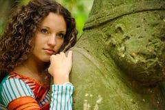A menina ao lado de um ídolo de pedra Imagens de Stock