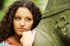 A menina ao lado de um ídolo de pedra Imagem de Stock Royalty Free