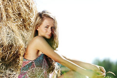 Menina ao lado de uma pilha de feno Fotografia de Stock Royalty Free