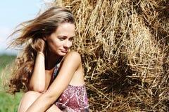 Menina ao lado de uma pilha de feno Fotografia de Stock