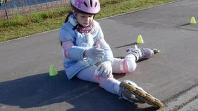 A menina após o acidente que senta-se no trajeto e faz massagens seu joelho video estoque