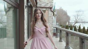 A menina apaixonado no vestido com violino à disposição anda e gerencie na câmera video estoque