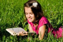 A menina aprecia ler Foto de Stock Royalty Free