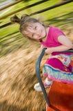 A menina aprecia o passeio do merry-go-round Fotos de Stock Royalty Free