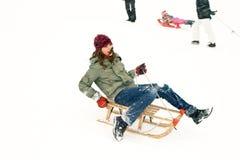 A menina aprecia sledging no inverno Imagens de Stock