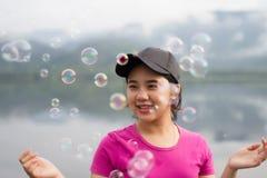 A menina apreciam seu lifestlye e felizes tailandeses com bolhas de ar Imagens de Stock