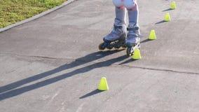 A menina aprende à patinagem de rolo entre cones vídeos de arquivo
