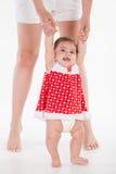 A menina aprende andar com a mamã pela mão foto de stock