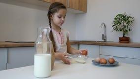 A menina aprende cozinhar na cozinha e fazer a padaria video estoque