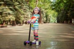 A menina aprende montar o 'trotinette' em um parque no dia de verão ensolarado Foto de Stock