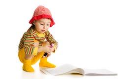 A menina aprende pintar no álbum. imagem de stock