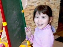 A menina aprende tirar Foto de Stock
