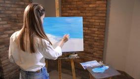 A menina aprende tirar Toma a pintura azul na paleta e põe-na sobre a lona 4K mo lento vídeos de arquivo