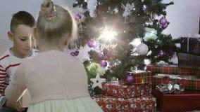 A menina apresenta a menino um presente do Natal filme