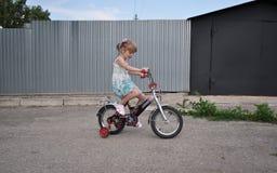 A menina aproximadamente cinco anos velho aprende montar uma bicicleta imagens de stock royalty free