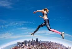 Menina apta de salto através do céu azul foto de stock