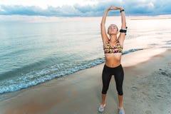 Menina apta dos jovens que medita sobre a praia no nascer do sol Fotografia de Stock Royalty Free