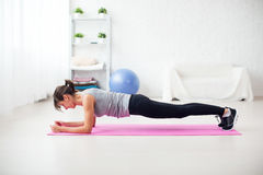 Menina apta na posição da prancha sobre a esteira em casa o exercício da sala de visitas para a aptidão traseira dos pilates do c fotografia de stock